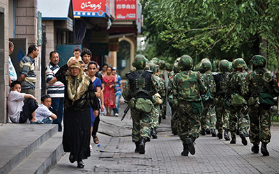 Chinese soldiers patrol the streets of a Uyghur neighbourhood