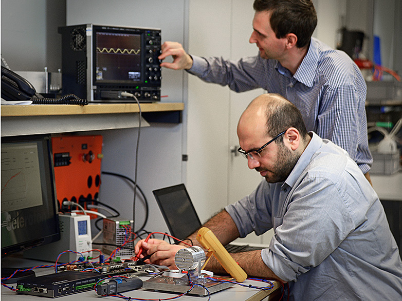 Arda Tüysüz (ETH/PES, in front) and an employee of Celeroton work on the new ultra-fast motor in their laboratory.