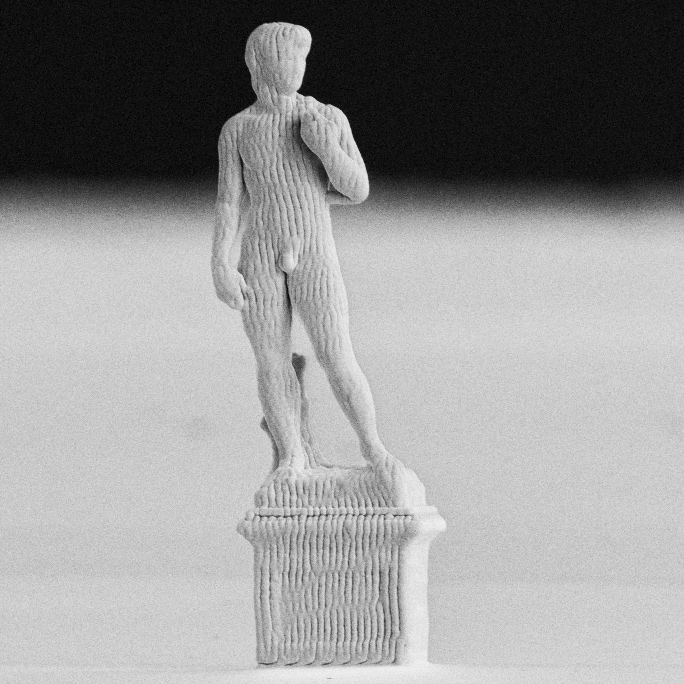 tiny statue of standing man with vertical ridges resembling corduroy