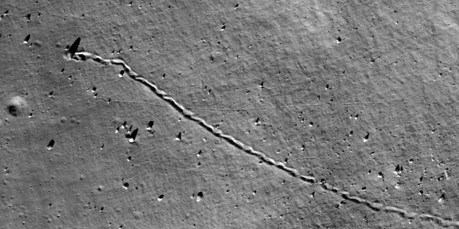 A rock has rolled over the moon's surface leaving a long groove behind it