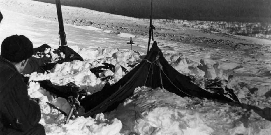two people look at destroyed tent in snow