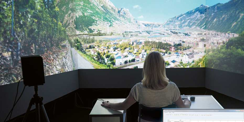 Woman sitting in virtual reality lab with landscape images
