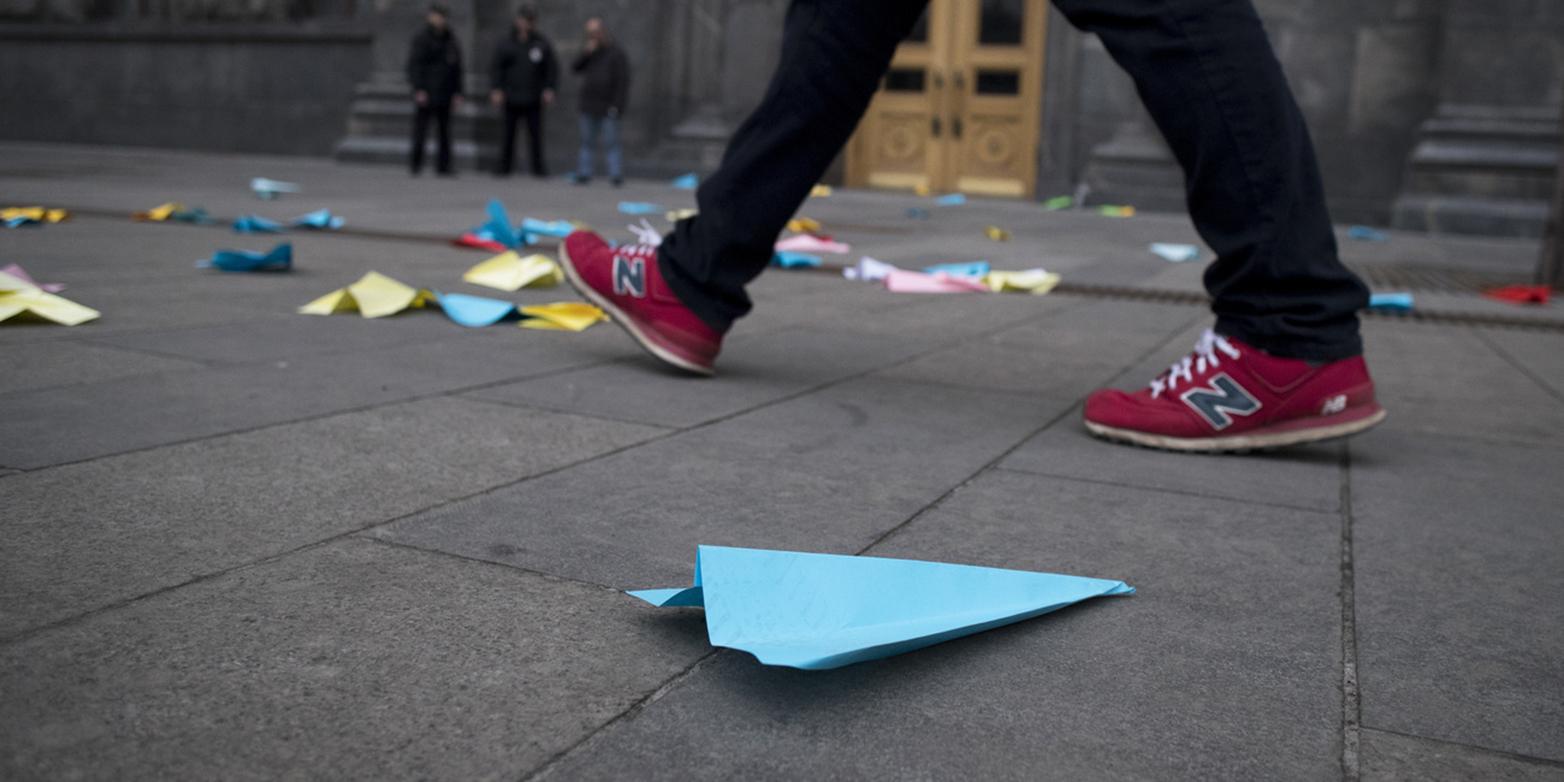 Blue paper aeroplane lies on the asphalt